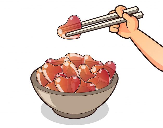 Gelatine disegnate a mano del cuore nella ciotola con le bacchette per il giorno di biglietti di s. valentino