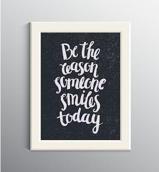 Citazione disegnata a mano, frase. ottimista, poster di lettere di saggezza, carta. sii il motivo per cui qualcuno sorride oggi. cornice bianca sul muro.