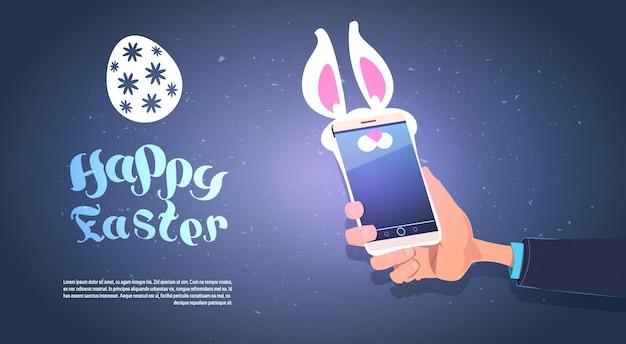 Smart phone della tenuta della mano con bunny ears fondo felice di pasqua