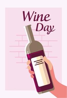 Mano che tiene la bottiglia del giorno del vino