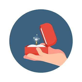 Mano che tiene una scatola e anello aperto per impegnarsi, mostra un anello di diamanti.