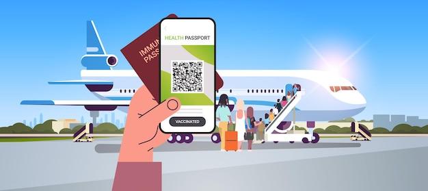 Mano che tiene il certificato di vaccinazione digitale e il passaporto di immunità globale vicino all'immunità del coronavirus dell'aeroplano