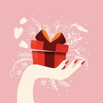 Mano che tiene una confezione regalo con cuori che escono e decorazioni. illustrazione disegnata a mano colorata per happy valentines day. biglietto di auguri con fogliame ed elementi decorativi.