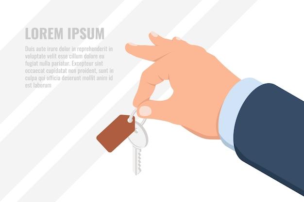 Mano che tiene la chiave con etichetta, casa o chiave dell'automobile