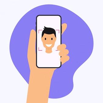 Mano che tiene il cellulare smart phone con l'app di riconoscimento facciale.