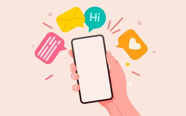 Mano che tiene il telefono con la comunicazione dei messaggi e il concetto di social network