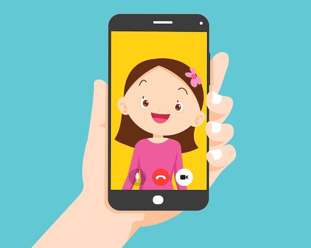 Mano che tiene lo smartphone con la ragazza dei bambini sullo schermo videochiamata con studente carino