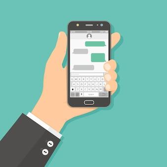 Mano che tiene smartphone con app di messaggistica sms
