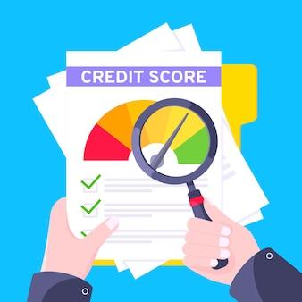 La mano tiene l'indicatore del tachimetro dell'indicatore del punteggio di credito con i livelli di colore su fogli di carta