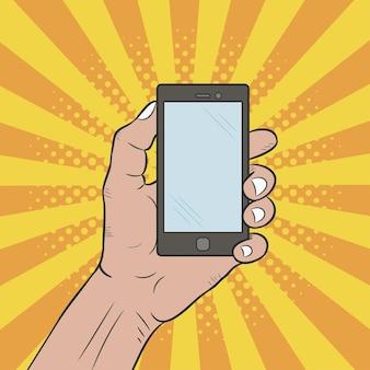 La mano tiene un telefono cellulare illustrazione pop art disegnata a mano su sfondo a raggiera comica