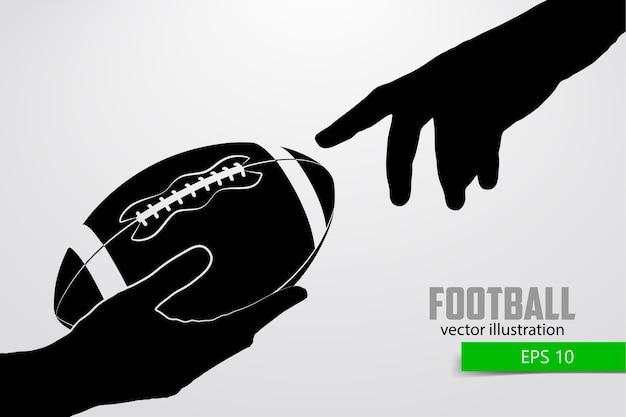 La mano tiene il pallone da rugby, silhouette. rugby. football americano
