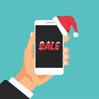 La mano tiene lo smartphone con il cappello di babbo natale telefono come un regalo per il concetto di vendita di capodanno e natale
