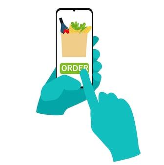 Una mano in un guanto protettivo tiene uno smartphone e ordina il cibo nell'app senza contatto sicuro