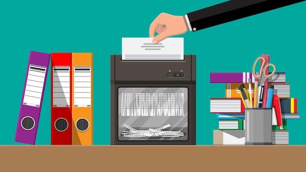 Mano che mette la carta per documenti nella macchina trituratrice. documento strappato a brandelli.