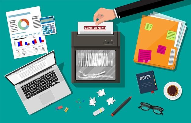 Mano che mette la carta nella macchina del trituratore. concetto di risoluzione del documento. tavolo con laptop di carta, calcolatrice, fogli, penna, raccoglitore ad anelli.