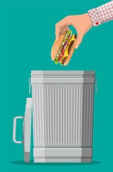 Mano che getta hamburger nel cestino della spazzatura