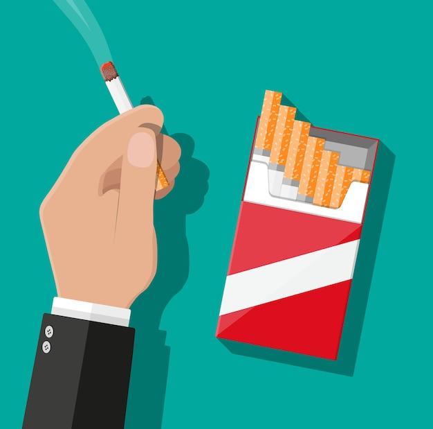 Mano con sigaretta e pacchetto di sigarette