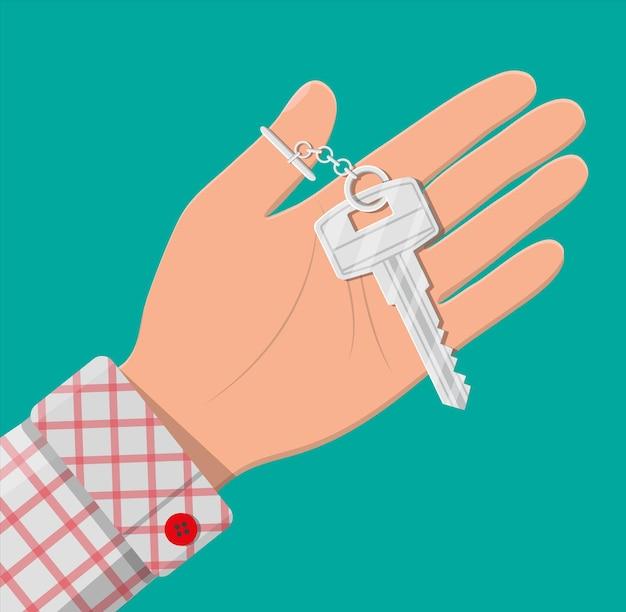 Mano con chiave in metallo. immobiliare, mutuo, vendita auto, affitto appartamenti o casa. illustrazione vettoriale in stile piatto