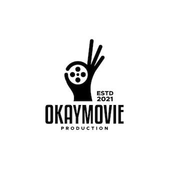 Una mano con un gesto ok e una forma di bobina di film buona per qualsiasi attività legata ai film