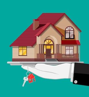 Mano con piccola casa e illustrazione delle chiavi