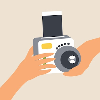 Le mani tengono la fotocamera per scatti istantanei