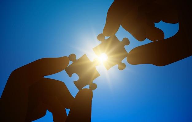 Le mani tengono un puzzle sulla luce solare