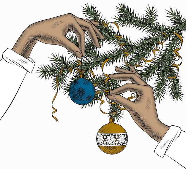 Mani che tengono una palla dell'albero di natale con un nastro