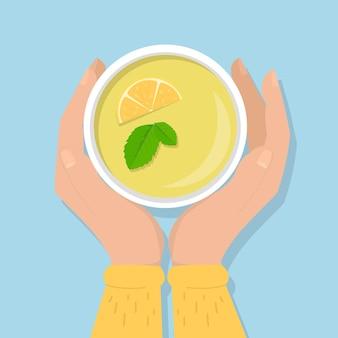 Mani che tengono tazza di tè verde con un limone