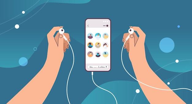 Mani che tengono gli auricolari comunicano in messaggistica istantanea tramite messaggi vocali applicazione chat audio social media concetto di comunicazione online illustrazione vettoriale orizzontale