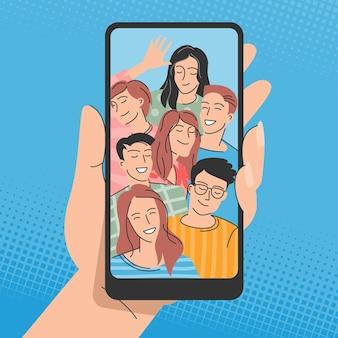 Mani che tengono il telefono cellulare con amici felici sullo schermo. giovani in posa per selfie