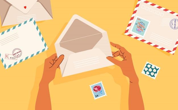 Mani in possesso di una busta aperta. buste, francobolli postali e cartoline sul tavolo. vista dall'alto. banner illustrato moderno, design della carta. concetto di corrispondenza e consegna postale.