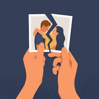 Mani che tengono una foto strappata di una coppia innamorata. il concetto di divorzio, separazione e cuore spezzato