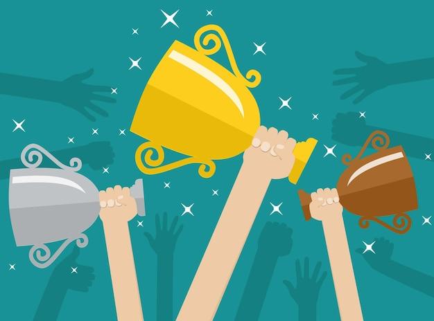 Mani che tengono le tazze del vincitore dei trofei