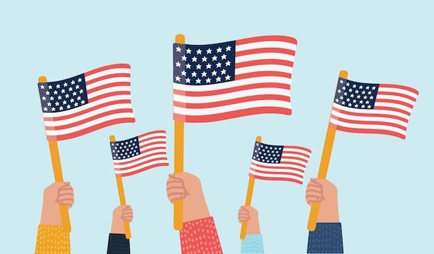 Mani che tengono in alto le bandiere americane