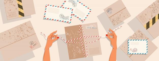 Mani e pacchi sul tavolo. vista dall'alto verso il basso. scatole di consegna, cartoline con francobolli e buste sul tavolo. le mani legano una corda e preparano la scatola per la spedizione. consegna pacchi e affrancatura.