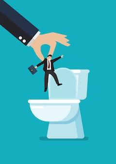 Le mani gettano un uomo d'affari nella tazza del water.
