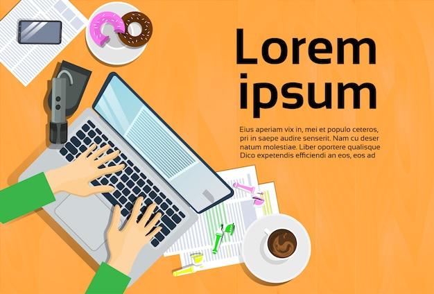 Mani che scrivono sul computer portatile, sulla vista superiore sullo smart phone dello scrittorio e sulle note sul concetto di carta del posto di lavoro