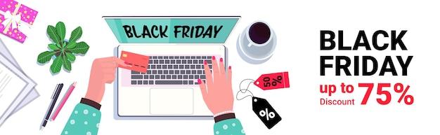 Mani utilizzando laptop shopping online venerdì nero vendita sconti vacanze concetto di e-commerce sul posto di lavoro scrivania vista dall'alto