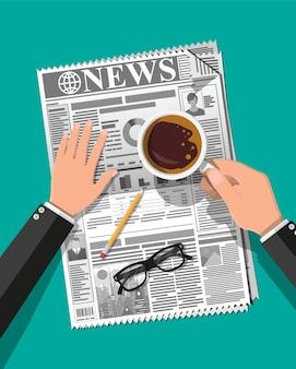 Mani con giornale tazza di caffè, occhiali da vista, matita
