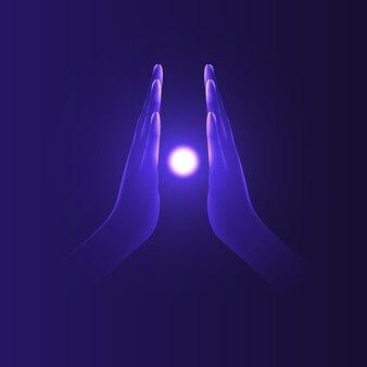 Mani con i palmi premuti l'uno contro l'altro tra i quali c'è una luminosa palla di energia. concentrazione, rilassamento, aiuto, yoga, concetto di fede.