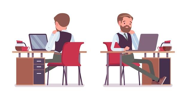 Impiegato di ufficio maschio bello che si siede allo scrittorio