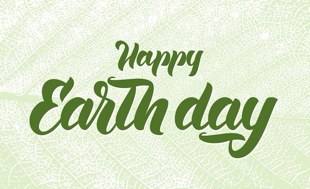 Lettere scritte a mano di happy earth day su sfondo texture foglia