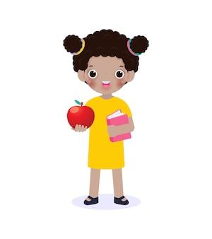 Felice bambina nera americana in piedi e tenendo il libro con la mela