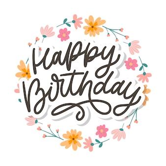Buon compleanno lettering slogan di calligrafia con fiori
