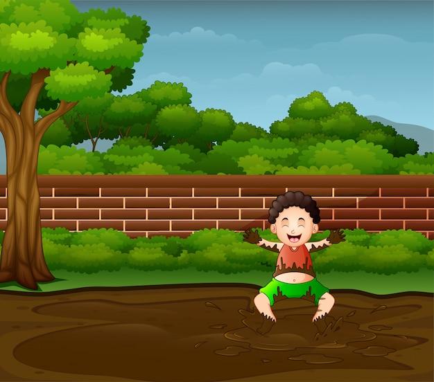 Ragazzo felice che gioca nel fango