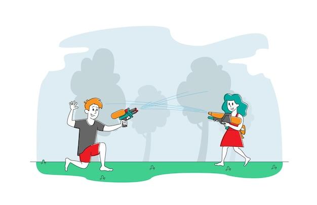 Fratello e sorella felici che giocano a tiro con pistole ad acqua