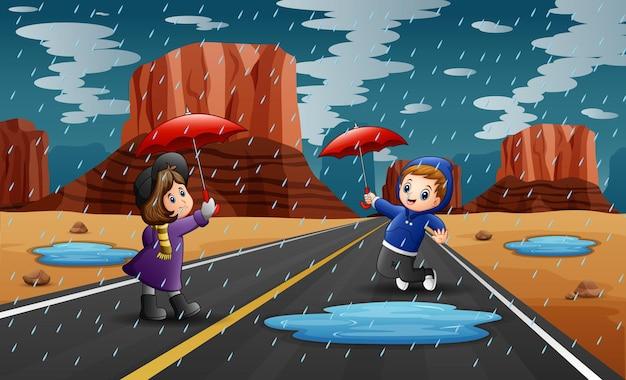 Bambini felici che tengono ombrello sotto la pioggia
