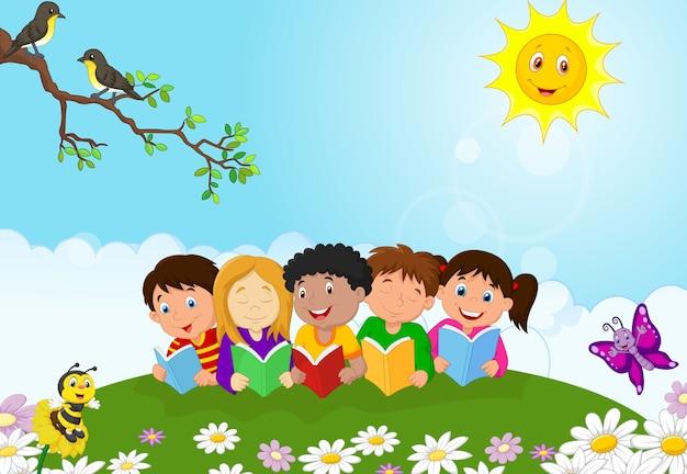 Bambini felici sdraiati sull'erba durante la lettura di libri