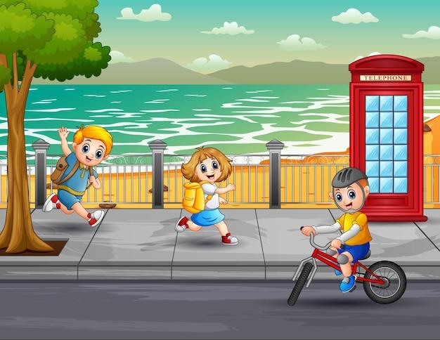 Bambini felici che corrono e vanno in bicicletta per strada