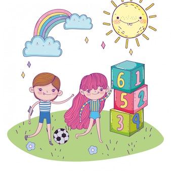 Il giorno, il ragazzo e la ragazza dei bambini felici con pallone da calcio e i blocchi di numeri parcheggiano